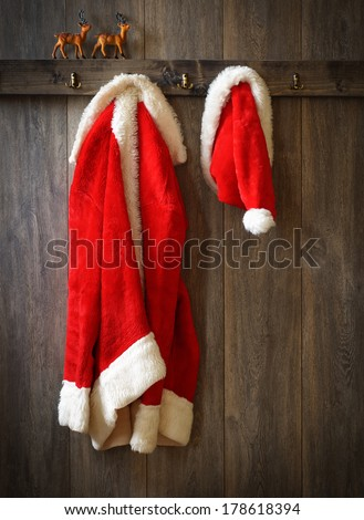 Santa's coat and hat hanging up with reindeer on ledge - stock photo
