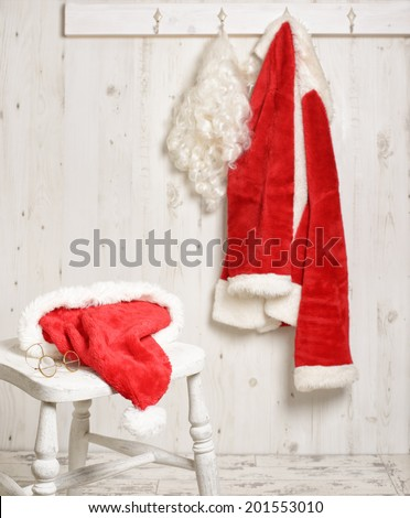 Santa's hat and gold rimmed specs on stool with coat hanging in the background - stock photo