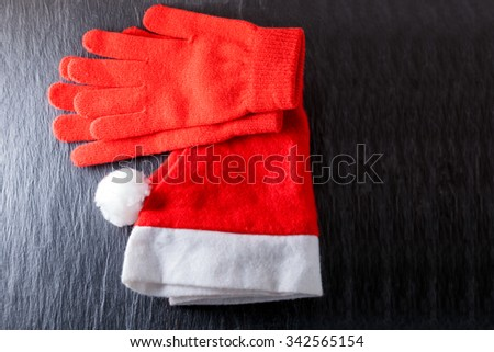 Santa's hat  and red gloves on black background