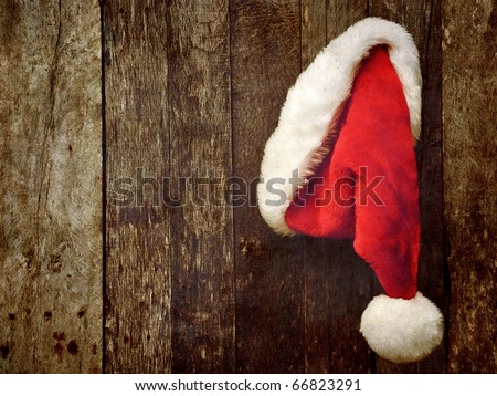 Santa's hat hanging on a rustic wooden backdrop with copy space.  Grunge textured. - stock photo