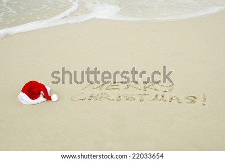 Santa's hat on a beach with Merry Christmas text - stock photo