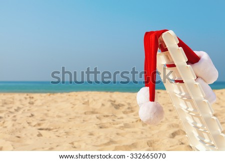 Santa's hat on on the chair at the beach - stock photo