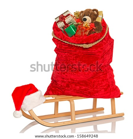 Santa's sack full of gift wrapped Christmas presents and toys including a handmade bear on a wooden sledge, isolated on a white background. - stock photo