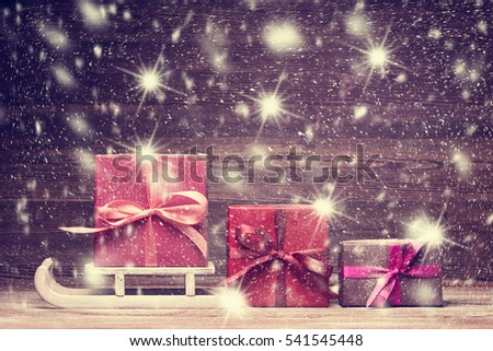 Santa's sledge and set of gift boxes over snowy background