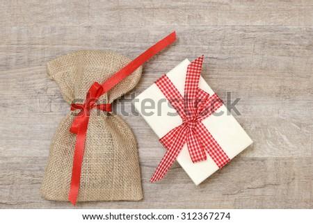 santa sac and xmas present lying on wood  - stock photo