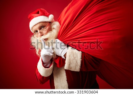 Santa showing shh gesture while carrying sack with xmas gifts - stock photo
