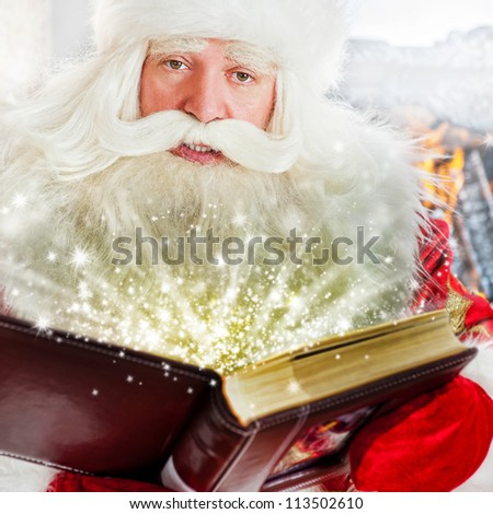 Santa sitting at the Christmas tree, fireplace and reading a book - stock photo