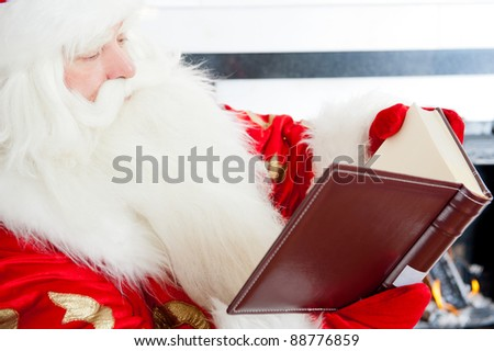 Santa sitting at the Christmas tree, near fireplace and reading a book. Indoors - stock photo