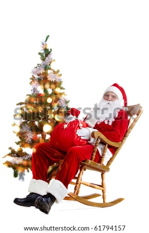Santa sitting in the armchair at the Christmas tree and holding a sack isolated on white - stock photo