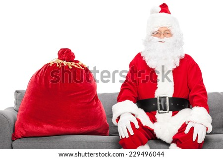 Santa sitting on a sofa with a bag full of presents next to him isolated against white background - stock photo
