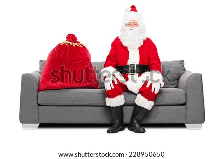 Santa sitting on a sofa with a bag of presents next to him isolated on white background - stock photo