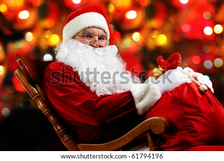 Santa sitting with a sack against sparkling lights - stock photo