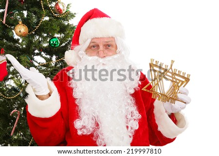 Santa standing in front of a Christmas tree holding a menorah.   - stock photo