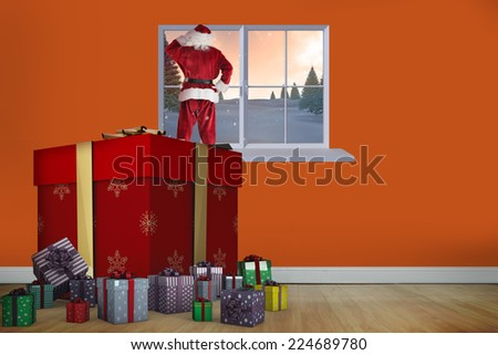 Santa standing on giant present against room with wooden floor - stock photo
