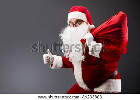 Santa with a sack looking at camera and showing thumb up - stock photo