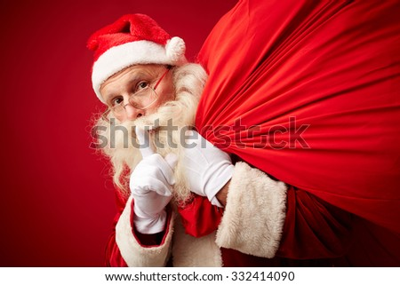 Santa with sack of xmas gifts asking for silence - stock photo