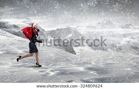 Santa woman running with red gift bag on back - stock photo