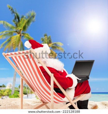 Santa working on laptop on a tropical beach seated on a sun lounger shot with a tilt and a shift lens - stock photo
