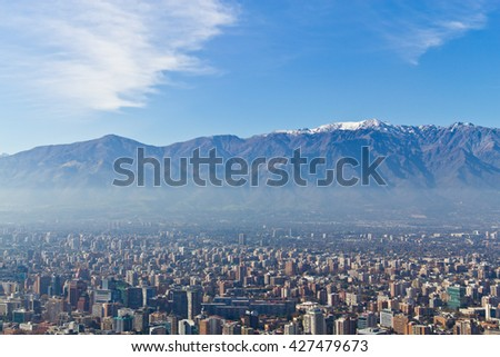Santiago cityview from Cerro San Cristobal. Buldings can be seen in front of snowy moutains and blue sky. Pollution is present too.