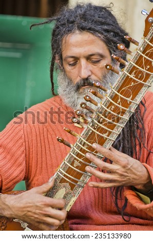 SANTIAGO DE COMPOSTELA, SPAIN - JULY 14, 2014: A man with white slime and hindu garb, plays the sitar in one of the streets of the historic town. - stock photo