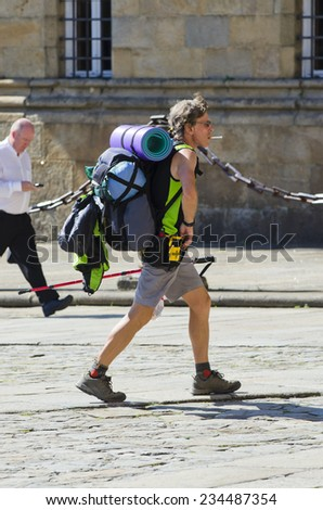 SANTIAGO DE COMPOSTELA, SPAIN - JULY 11, 2014: Detail of a pilgrim, carrying their backpacks, in the historic town. - stock photo