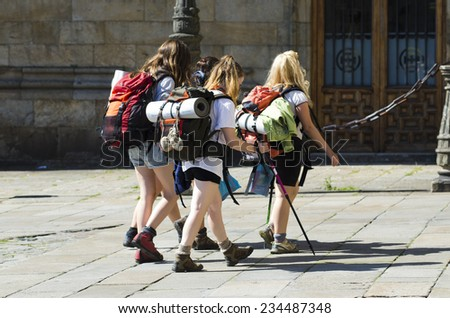 SANTIAGO DE COMPOSTELA, SPAIN - JULY 11, 2014: Detail of some pilgrims, carrying their backpacks, in the historic town. - stock photo