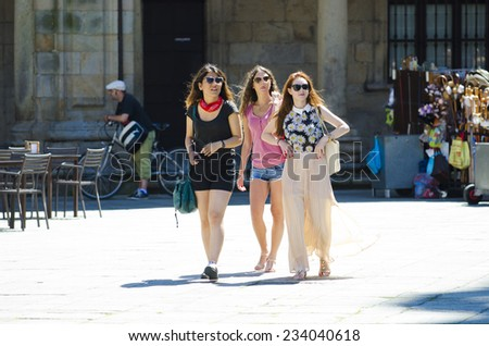 SANTIAGO DE COMPOSTELA, SPAIN - JULY 11, 2014: Three attractive young stroll through the old town, a sunny summer day. - stock photo