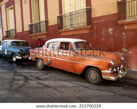 SANTIAGO DE CUBA, CUBA - NOVEMBER 30:  Two american vintage car parked along a colored facade ,on november 30, 2014, in Santiago de Cuba, Cuba  - stock photo