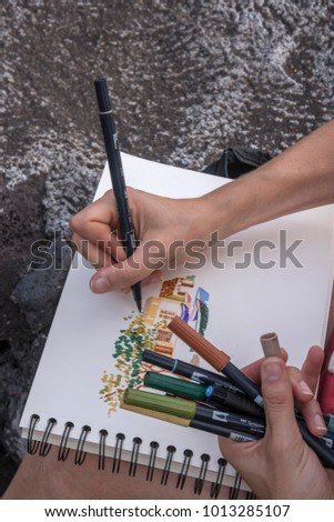 Santiago island, Cape Verde - september 02, 2015: Scene with hands of a young tourist drawing the surroundings, in front of the beaches of Ciudad Velha