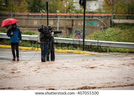 SANTIAGO, REGION METROPOLITANA / CHILE - APRIL 17 2016 - Unidentified reporter inside flooded street at Santiago after heavy rains.