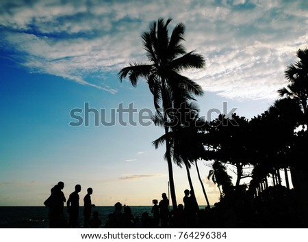 Santo Domingo, Dominican Republic - February 27, 2016 : Silhouette of unknown people standing on the side walk (malecon) next to the sea at sunset time