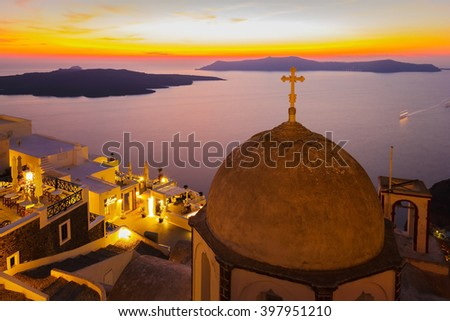 Santorini at night with view of Nea Kameni volcanic island and twilight sky above Mediterranean sea, Greece (selective focus on cross at top of church) - stock photo