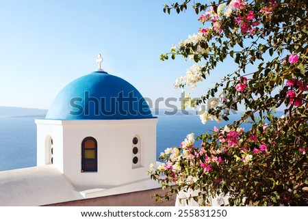 Santorini, classic view of blue dome church with Bugambilia Flowers. Oia Village, Greece. - stock photo