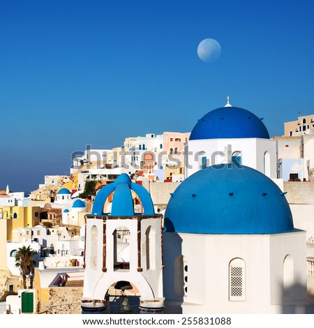 Santorini, classic view of blue dome churches with moon. Oia Village, Greece. - stock photo