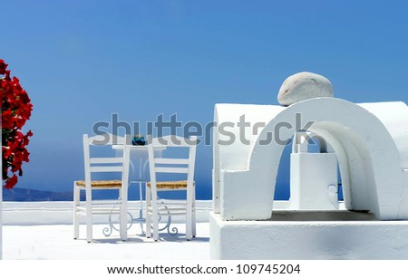 Santorini cosy terrace with two chairs and flowers - stock photo