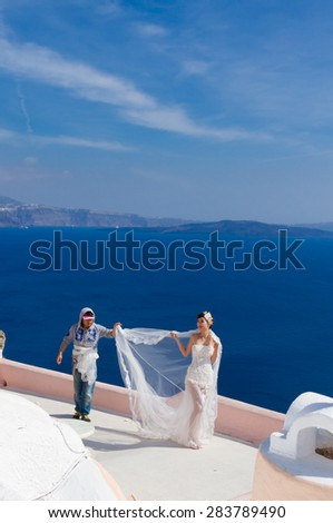SANTORINI - GREECE on 8 of MAY 2014: Photographer styling bride for wedding photoset against blue Aegan Sea, Oia, Santorini, Greece on 8 may, 2014