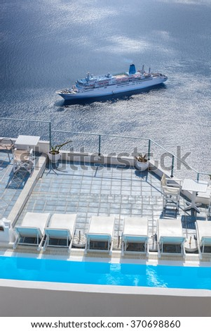 Santorini island with swimming pool against ship in Greece - stock photo