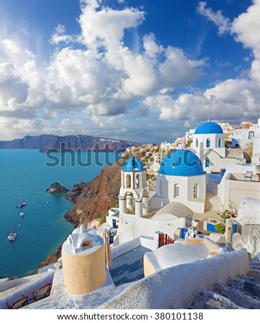 Santorini - The look to typically blue church cupolas in Oia over the caldera and the Therasia island in the background. - stock photo