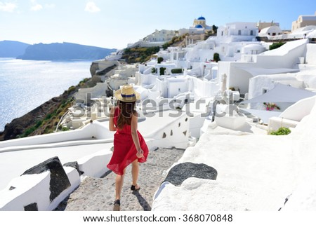 Santorini travel tourist woman on vacation in Oia walking on stairs. Person in red dress visiting the famous white village with the mediterranean sea and blue domes. Europe summer destination