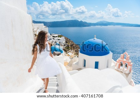 Santorini travel tourist woman on vacation in Oia walking on stairs. Person in white dress visiting the famous white village with the mediterranean sea and blue domes. Europe summer destination - stock photo