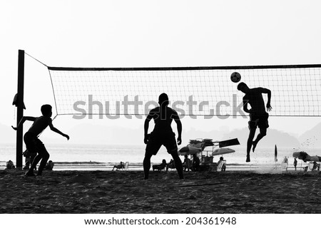 SANTOS, BRAZIL - March 01, 2012: group of young people playing footvolley on the beach in Santos in March 01, 2012