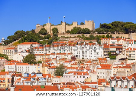 Sao Jorge (Saint George) castle over the old rooftops of Lisboa downtown. Portugal - stock photo