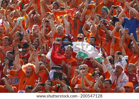 SAO PAOLO, BRAZIL - JUNE 23, 2014: Fans celebrate during the World Cup Group B game between the Netherlands and Chile at the Arena Corinthians. NO USE IN BRAZIL. - stock photo