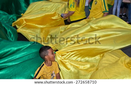 SAO PAULO, BRAZIL - APRIL 12, 2015: One unidentified boy in the middle of brazilian flag at protest against federal government corruption in Sao Paulo Brazil. - stock photo