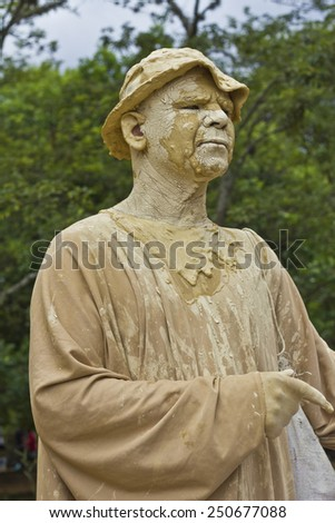 SAO PAULO, BRAZIL - FEBRUARY 01, 2015: An unidentified man executing a popular living statue performance covered with mud in one street of Ibirapuera Park at Sao Paulo Brazil. - stock photo
