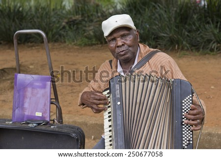 SAO PAULO, BRAZIL - FEBRUARY 01, 2015: An unidentified street musician singing and playing one old accordion in the Ibirapuera Park at Sao Paulo Brazil. - stock photo