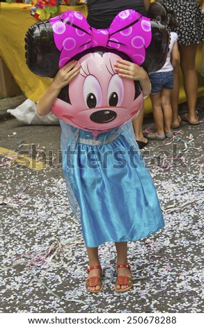 SAO PAULO, BRAZIL - JANUARY 31, 2015: An unidentified girl dressed like a princess with a Minnie balloon in front her face participate in the annual Brazilian street carnival dancing and singing samba. - stock photo