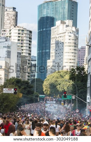 SAO PAULO, BRAZIL - June 7, 2015: crowd at the gay parade, with building the center of the city in the background, in the 19th Gay Pride Parade Sao Paulo - stock photo