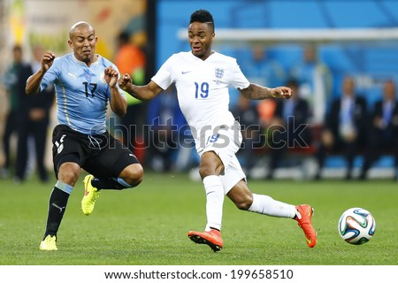 SAO PAULO, BRAZIL - June 19, 2014: Egidio Arevalo Rios of Uruguay and Raheem Sterling of England compete for the ball during the game between Uruguay and England at Arena Corinthians. No Use in Brazil - stock photo