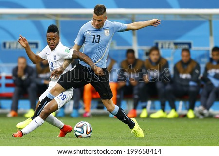 SAO PAULO, BRAZIL - June 19, 2014: Jose Gimenez of Uruguay and Raheem Sterling of England compete for the ball during the game between Uruguay and England at Arena Corinthians. No Use in Brazil - stock photo